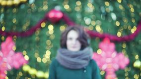 有大围巾的美丽的少女微笑户外在冬天,圣诞灯背景的 a室外冬天画象  影视素材