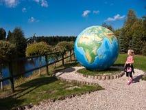 有大地球的女孩在恐龙主题乐园, Leba,波兰 库存照片