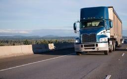 有大块拖车的蓝色半天小室卡车在宽平直的highw 免版税库存图片