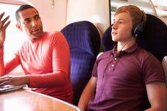 年轻有大声的音乐的人干扰的火车乘客 库存照片