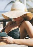 有大夏天帽子和雪茄的美丽的妇女 免版税图库摄影