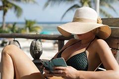 有大夏天帽子和雪茄的美丽的妇女 免版税库存图片