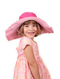 有大帽子和礼服的愉快的小女孩 免版税库存照片