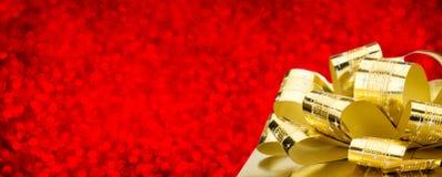 有大弓的金黄礼物盒在红色bokeh白色迷离背景, 免版税库存照片
