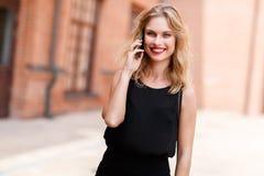 有大微笑的美丽的金发碧眼的女人谈话在电话户外 免版税库存图片