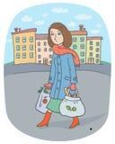 有大手提袋的年轻女人从城市市场去回家