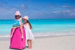 有大搜寻在热带海滩的手提箱和地图的小女孩方式 免版税库存照片