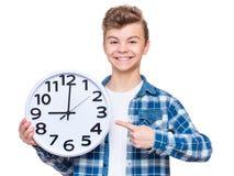 有大时钟的青少年的男孩 免版税库存照片