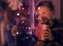 有大杯子的小男孩热的饮料在与Christmass光的窗口看 免版税库存图片