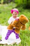 有大棕色女用连杉衬裤的逗人喜爱的矮小的愉快的女婴涉及绿草草甸、春天或者夏季 免版税库存照片