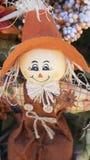 有大橙色帽子微笑的逗人喜爱的稻草人玩偶 免版税库存图片