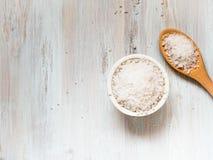 有大海盐和木匙子的白色碗在白色木桌上 免版税库存照片