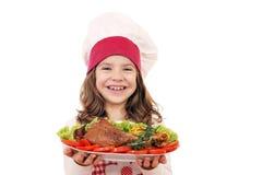 有大火鸡鼓槌的小女孩厨师 库存照片