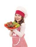 有大火鸡鼓槌的小女孩厨师 免版税图库摄影