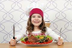有大火鸡鼓槌的小女孩厨师 免版税库存照片