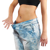 有大牛仔裤减重的妇女 库存照片