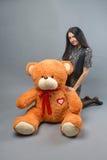 有大玩具熊软的玩具愉快微笑和使用的年轻美丽的女孩在灰色背景 库存照片