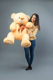 有大玩具熊软的玩具愉快微笑和使用的年轻美丽的女孩在灰色背景 免版税库存照片