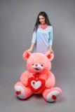 有大玩具熊软的玩具愉快微笑和使用的年轻美丽的女孩在灰色背景 库存图片