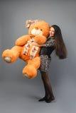 有大玩具熊软的玩具愉快微笑和使用的年轻美丽的女孩在灰色背景 免版税库存图片