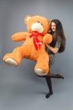 有大玩具熊软的玩具愉快微笑和使用的年轻美丽的女孩在灰色背景 免版税图库摄影