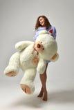 有大玩具熊软的玩具愉快微笑的年轻美丽的女孩 免版税库存图片