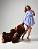 有大玩具熊软的玩具愉快微笑的年轻美丽的女孩 免版税图库摄影