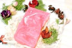 有大理石纹理的桃红色肥皂在绿色青苔旁边干花和片断的桌上  免版税库存图片