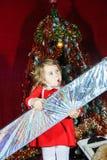 有大甜圣诞节礼物的逗人喜爱的小女孩 免版税库存图片