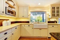 有大白色水槽和经典设计的奶油色颜色厨房 免版税库存照片