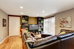 有大皮革长沙发和电视的家庭娱乐室 图库摄影