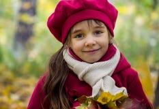 有大眼睛的一个小美丽的女孩微笑在温暖的秋天的,穿一顶桃红色贝雷帽和一件外套有干燥叶子的在手上 库存图片