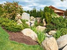 有大石头和具球果植物的一个庭院倾斜的 免版税库存图片