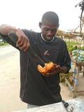 有大砍刀的人吃软的椰子。 库存图片