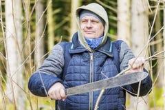 有大砍刀的远足者在森林里 免版税库存照片