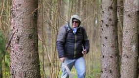 有大砍刀的远足者,在森林里挑运一台片剂个人计算机 股票视频