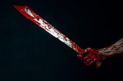 有大砍刀蛇神邪魔疯子刀子的血淋淋的手 免版税库存图片