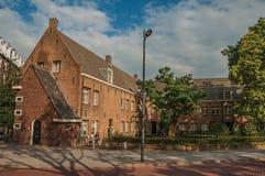 有大砖房子的街道,树在庭院和人们坐在日落和蓝天在s斯海尔托亨博斯 免版税库存图片