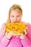 有大碗的兴高采烈的妇女不健康的油炸马铃薯片 免版税图库摄影