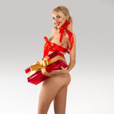 有大礼物的妖娆的年轻白肤金发的女孩和在bo的红色丝带 库存图片