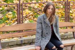 有大秋天哀伤的眼睛的美丽的女孩在外套和被剥去的黑牛仔裤坐一条长凳在秋天停放 图库摄影
