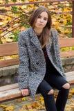 有大秋天哀伤的眼睛的美丽的女孩在外套和被剥去的黑牛仔裤坐一条长凳在秋天停放 免版税库存图片