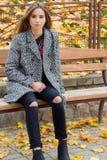 有大秋天哀伤的眼睛的美丽的女孩在外套和被剥去的黑牛仔裤坐一条长凳在秋天停放 免版税库存照片