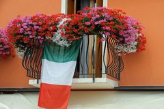 有大竺葵和意大利旗子的开花的阳台 免版税库存照片