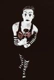 有大红色弓的戏剧性滑稽的小丑 库存图片