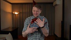 有大红色弓的POV有吸引力的男性得到的生日礼物箱子在舒适房子客厅 股票录像