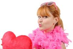有大红色心脏枕头的年轻美丽的妇女 免版税库存图片