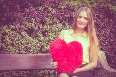 有大红色心脏的被迷恋的妇女 库存照片