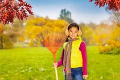 有大红色犁耙的快乐的亚裔女孩单独站立 库存照片