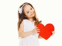 有大红色纸心脏的愉快的小女孩 库存图片